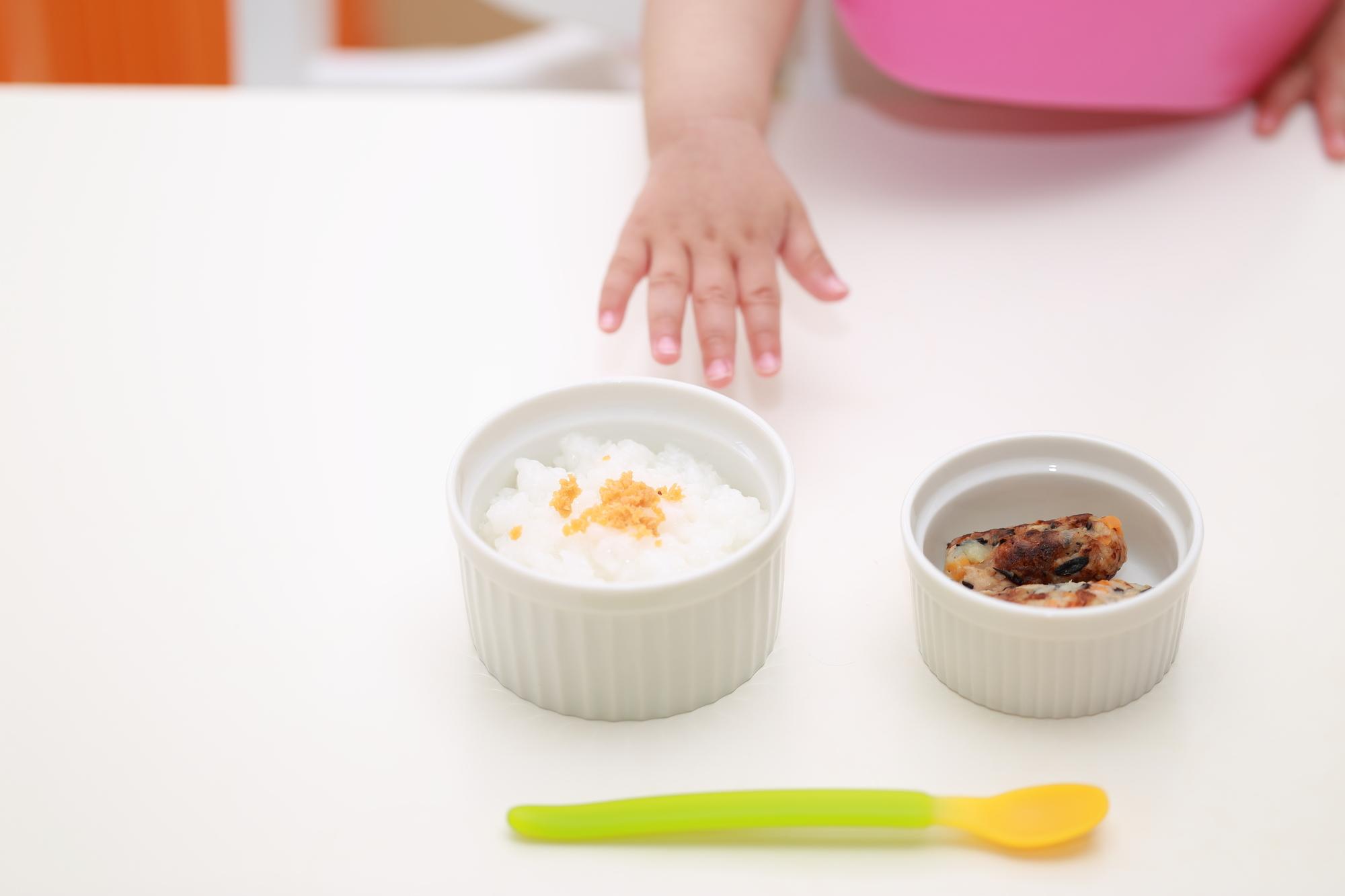 ご飯に手を伸ばす赤ちゃん